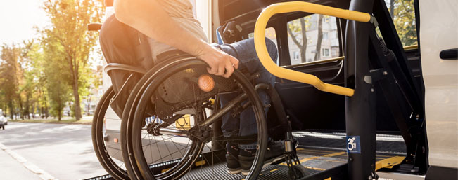 A man in a wheelchair on a lift of a vehicle for people with disabilities_