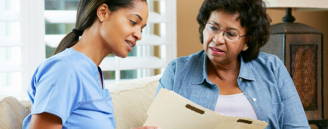 Female medical professional helping older woman