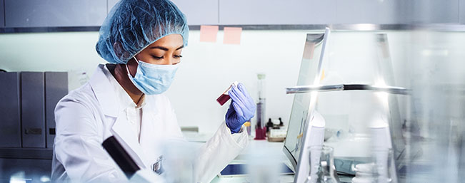 Lab tech examing a container of blood