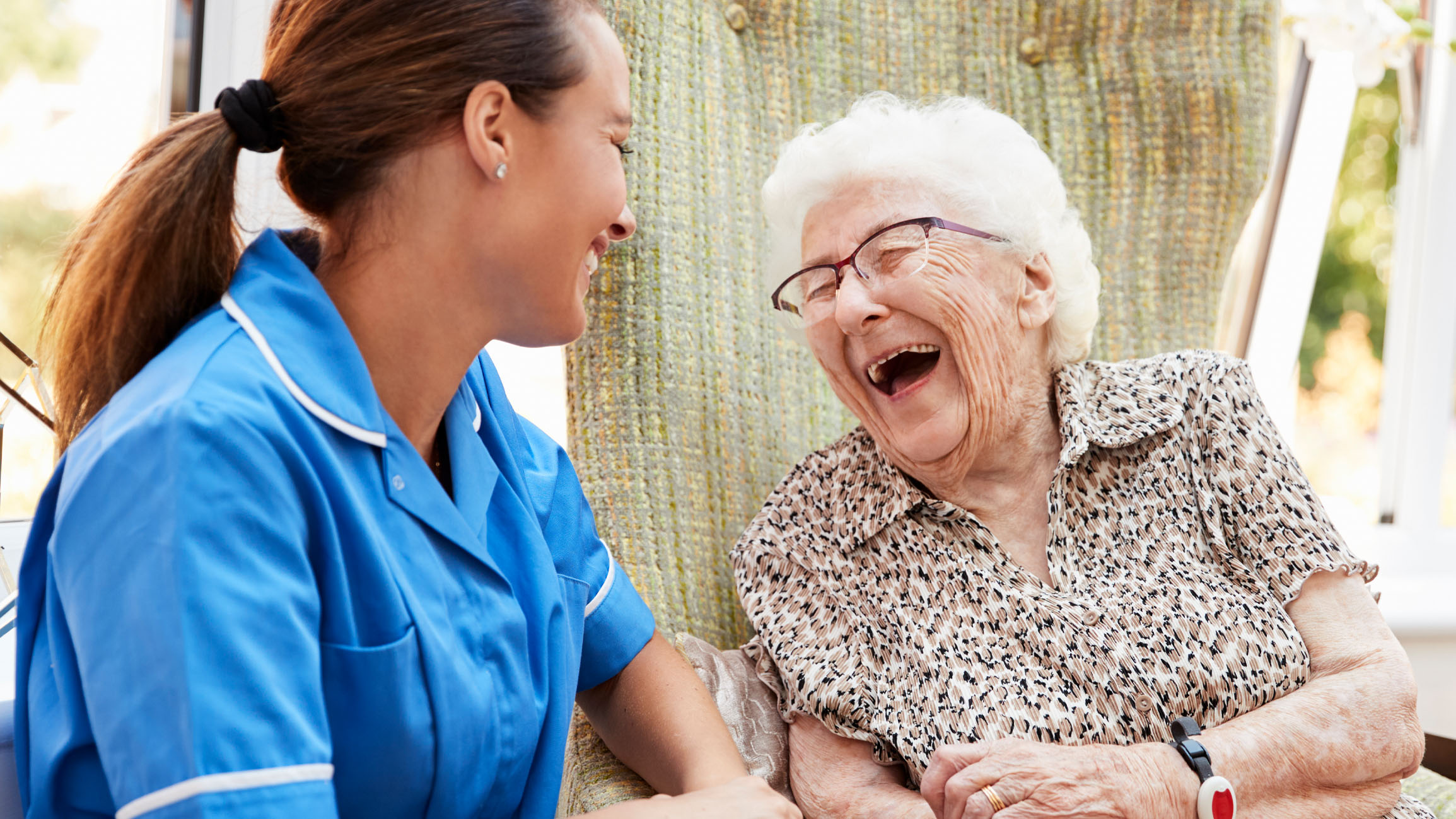 Medical professional and older woman laughing together