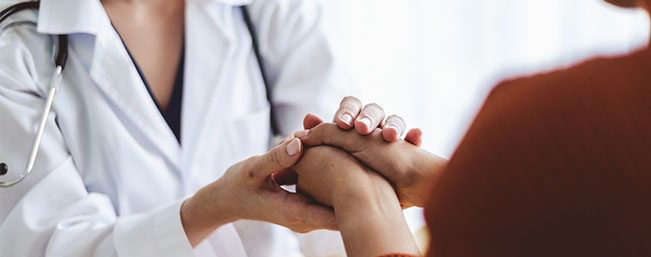 Two women compassionately holding hands